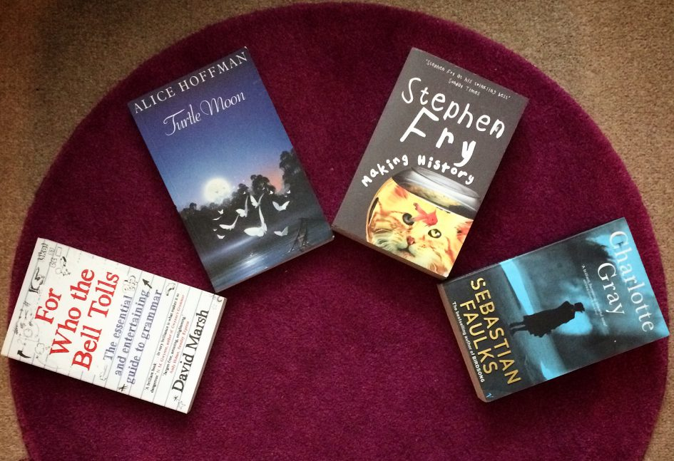 4 books spread out on a purple rug