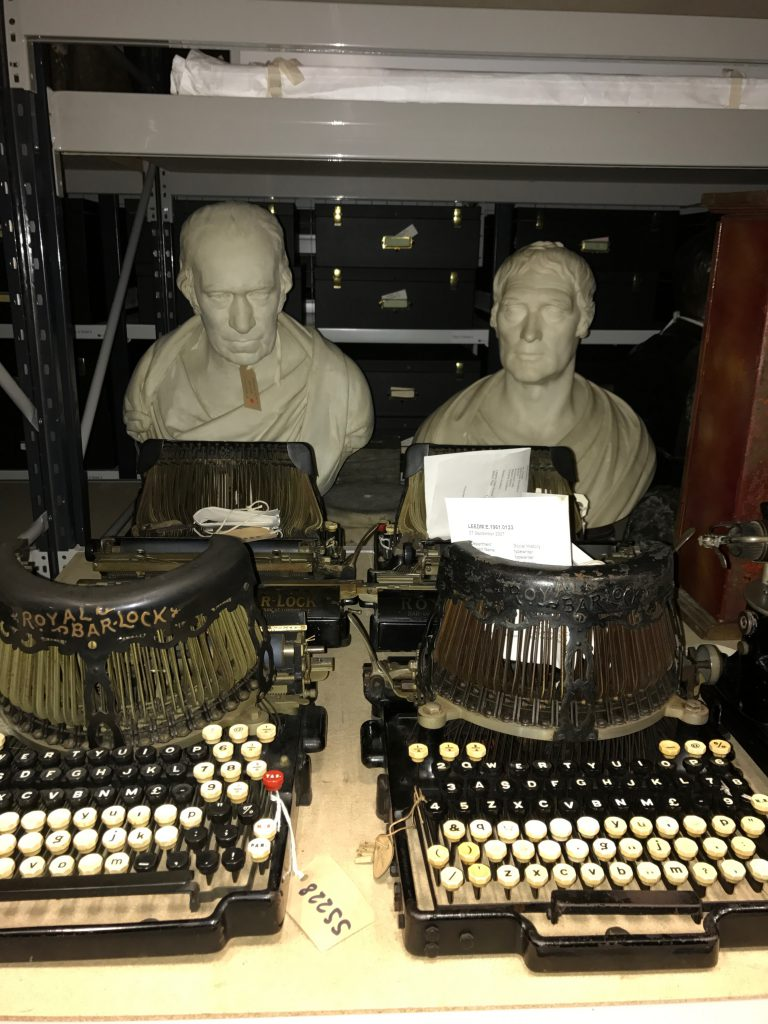 Two heads behind two typewriters